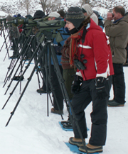Yellowstone wolf watchers lined up with spotting scopes: