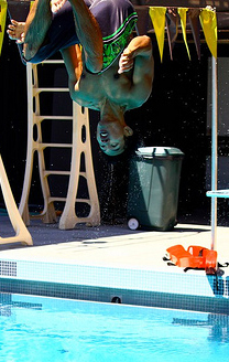 back flip photo by Joyce Kuo: swim student in mid air upside down during a back dive from a one meter diving board