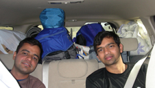 carpool brad and gear to ceiling.jpg: car interior with two passengers in backseat and gear piled to the ceiling