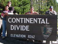 continental divide 2010 photo by Mark Nevill: four people stand behind sign that says continental divide