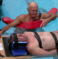 george and alan backboard practice: lifeguard with rescue tube, other lifeguard on backboard during a practice