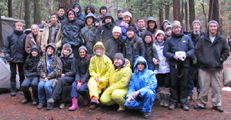 group photo 2014 Yosemite winter trip: 30 people in rain gear sitting or standing on a picnic table in a Yosemite campsite