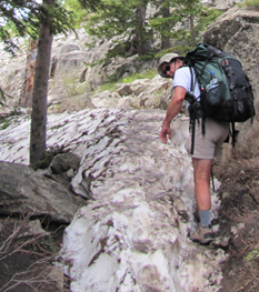 hiking through snowbanks cascade canyon June 2014: man with pack hiking through a large snowbank that covers the trail