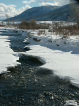 ice bridge, blowing snow on bank of Soda Butte creek: