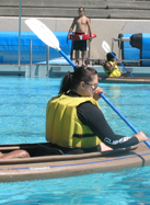 lifeguard Peter Lee guards kayak lesson at De Anza pool: lifeguard at edge of pool deck in background with paddlers in kayaks in pool in foreground