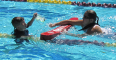 lifeguard approaches distressed child with faulty face mask: lifeguard spots and approaches a young swimmer as he grabs a lane line and holds his face mask in the other hand