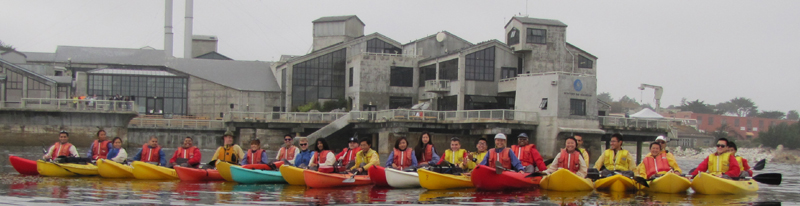 ocean kayak group photo Oct 20 2013 in front of aquarium: row of kayakers in front of the Monterey aquarium