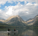 two paddlers on Leigh Lake morning 120 pixels.: two paddlers in a canoe on a lake in the morning with mountains behind
