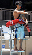 photo by Joyce Kuo lifeguard Herland Antezana activates emergency action plan: lifeguard stands in lifeguard station, blows whistle and points towards problem