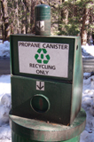 propane canister recycling only: a large trash can with a propane canister on top of it and a sign that says propane canister recycling only