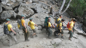 nps photo by Jeremy Bernfeld litter on Yosemite Falls trail: six people hold the sides of a wheeled litter bringing a victim down a trail, two other Yosemite Search and rescue people behind the litter