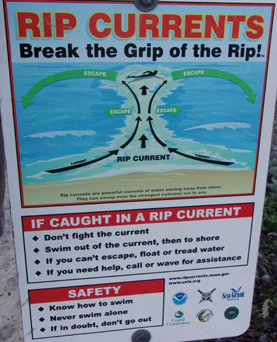 rip currents sign: sign at the beach with rip currents warnings