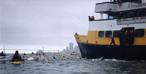 sharkfest: swimmer jumping off the ferry with the City skyline in the background and a kayak escort to the left