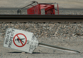 sign no trespass, rr tracks, shopping cart.: