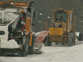 snowplows stay back: two snowplows, one with a sign that says stay back
