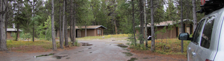 three cb cabins: three wood cabins and a road with big rain puddles