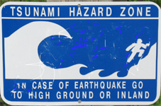 tsunami hazard zone sign 150 pixels: sign warning of a tsunami hazard zone with a drawing of a huge wave and a person climbing up a slope