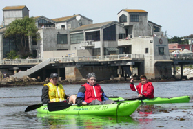 3 kayakers in front of Monterey Bay aquarium: