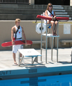 Alanna Klassen and Ethan Wilkie rotate guarding stations 1: one lifeguard at deck level, one in the lifeguard stand