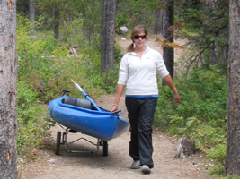Alanna Klassen portaging kayak: girl pulling a kayak on a wheeled trailer on a forested trail