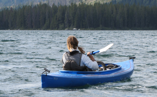 Alanna Klassen paddling against wind: girl in kayak with wind blown hair and whitecaps on water