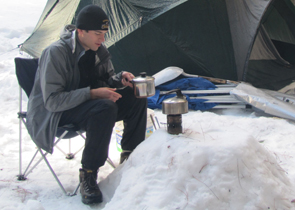 Alex Mitchell's snow table: a camper piled up snow to make a small table and has his stove on it, pan in hand to cook