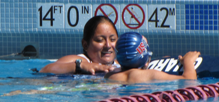 Christina Bolanos assists swimmer at Silicon Valley Kids triathlon 2012: Lifeguard with athlete at edge of the De Anza diving well