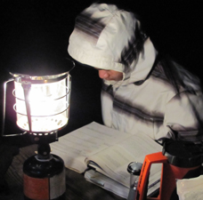 Jonathan Mai studies while camping 225 pixels: sitting at a picnic table reading by lantern light
