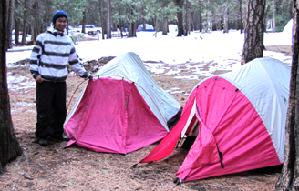 Jonathan with rain fly on upside down: guy stnading next to two tents of the same model, one with the rain fly on upside down