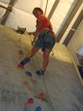 photot by Peter Ye Kelly Gomez at climbing gym: girl almost at the top of a route on a climbing wall