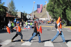 Old Bill's Fun Run volunteers Alanna Klassen, Emily Kinner and Alex Mitchell: three people crossing a crosswalk wearing orange vests, carrying flags