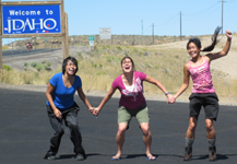 Phung, Kelly and Christina at Idaho border: three smiling grinning ladies with Idaho sign in background