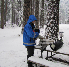 Quang packing up at end of winter 2011 trip: guy with gear on snow covered picnic table