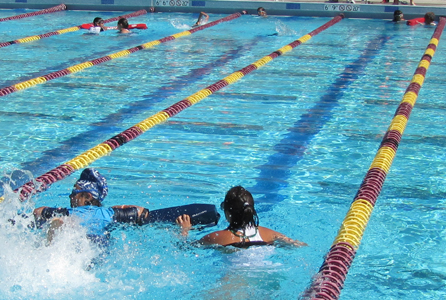 Wendy Tsang assists swimmer at Silicon Valley Kids Triathlon: lifeguard and swimmer in foreground, two other guards also assisting athletes in the background