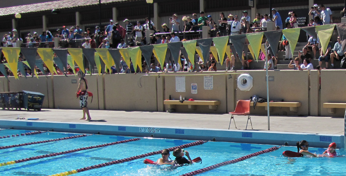 bleachers full of parents at kids triathlon: bleachers full of relatives and friends at kids triathlon, with two lifeguards in the water assiting swimmers