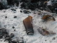 broken bottle in sand at campfire: broken beer bottle in sand at beach campfire area