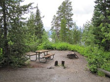 campsite at Signal Mountain: campsite with picnic table and firering, surrounded by trees, lake slightly visible in background