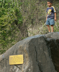child climbing on rock with warning sign about not climbing on the rocks:
