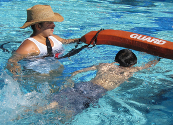 lifeguard Salina Martinez assists a swimmer at the Silicon Valley Kids triathlon: lifeguard wades with her rescue tube next to a distressed swimmer at a triathlon