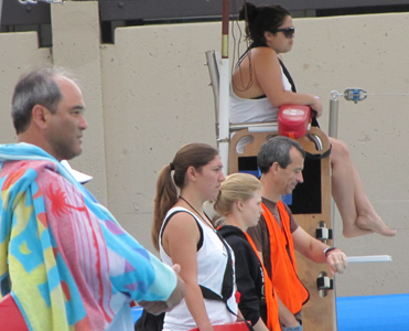 lifeguards and volunteers watch swimmers svkt 2011: lifeguards and volunteers watch swimmers, one lifeguard is wrapped in a towel after having just been in the water with a swimmer