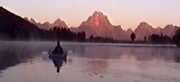 paddler and pink sunrise grand tetons: