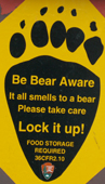 sign be bear aware in shape of footprint: