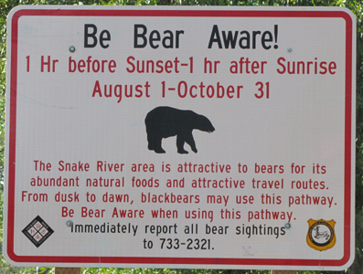 snake river pathway bear warning sign: a sign that says, in part, Be bear aware! one hour before sunset to one hour after sunrise August 1 to October 31. The sanke river area is attractive to bears for its' abundant natural foods and attractive travel routes. From dusk to dawn, blackbears may use this pathway. Be bear aware when using this pathway.