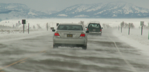 teton road with blowing snow: teton road with two cars and blowing snow