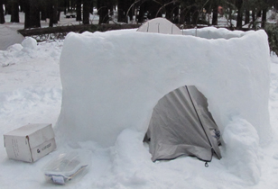 unfinished igloo with tent inside: unfinished igloo with tent pitched inside