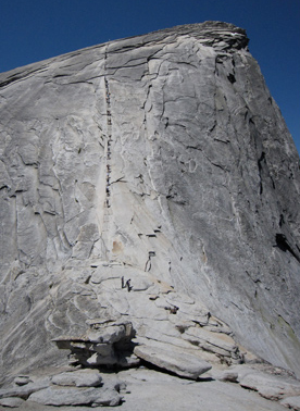 a tiny line of people going up a big rock face