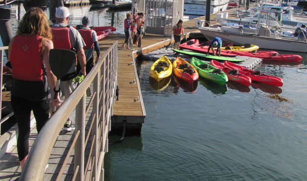 people walking down a ranp to a floating dock with kayaks