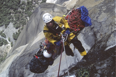 looking down from a helicopter to a rescuer on a basket litter