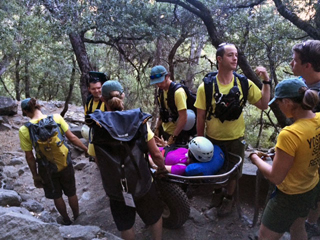 hiker on rescue litter who was injured trying to take a jumping photo to post on social media