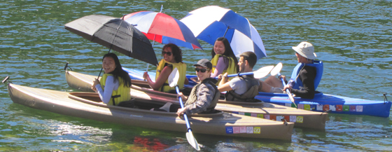 three kayaks, girls in the front holding large umbrellas, guys in the back paddling